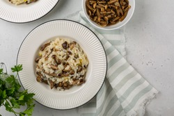 Risotto with honey mushrooms. Light grey background. Copy space. Two portions.