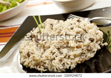 Risotto with mushrooms on black  tray and fork - stock photo