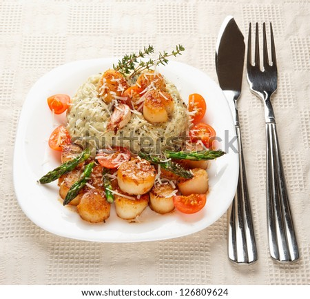 Risotto with pan seared sea scallops on restaurant table
