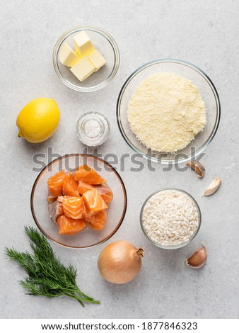 Risotto with salmon, lemon zest, parmesan and dill. Step by step cooking process. Risotto ingredients top view. Fresh salmon cubes, rice arborio, lemon, parmesan cheese, onion, garlic, butter and salt