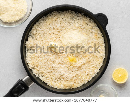 Risotto with salmon, lemon zest, parmesan and dill. Step by step cooking process. Step 6. Add parmesan cheese, butter, lemon zest to fried rice with chopped onion and garlic on black frying pan.
