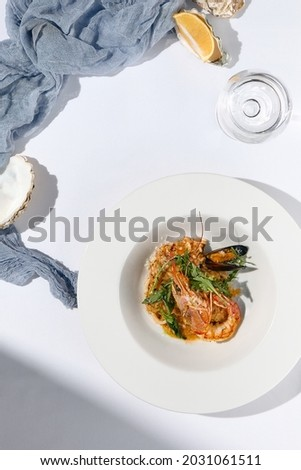 Risotto with seafood in contemporary style on white background. Italian risotto with prawn, mussels, squid in frutti di mare style. Summer dining with seafood and rice. Summer day seafood concept Stock fotó ©