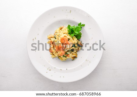 Shutterstock Risotto with shrimp. On a wooden background. Top view. Free space for your text.