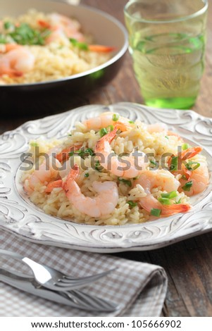 Risotto with shrimps and green onion on a rustic table - stock photo