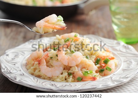 Risotto with shrimps and green onion on a rustic table