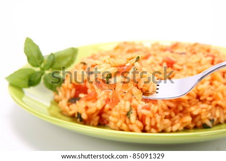 Risotto with tomatoes on a green plate decorated with basil being eaten with a fork