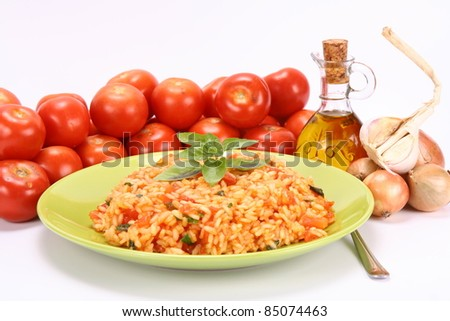 Risotto with tomatoes on a green plate decorated with basil with fresh tomatoes, onions, garlic and olive oil on white background