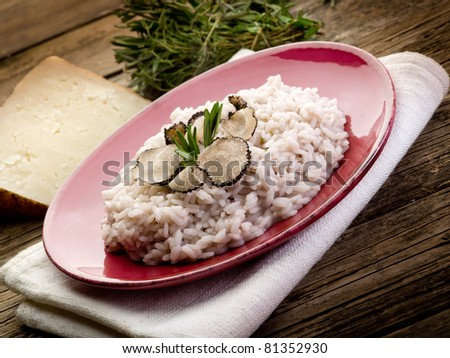 risotto with truffle over red dish - stock photo