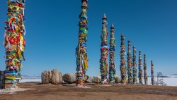 Ritual wooden pillars, tied with bright multi-colored ribbons, stand in a row. Nearby there are picturesque boulders. Background - clear blue sky, frozen ice lake Baikal.