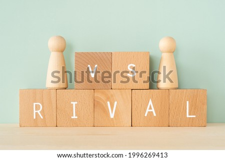 RIVAL; Wooden blocks with 'RIVAL' text of concept and human toys. Foto stock ©