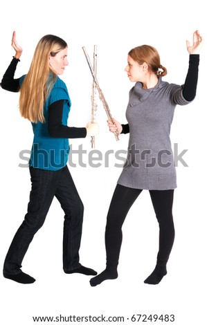 Rivalry between two young women with transverse flute isolated on white background.