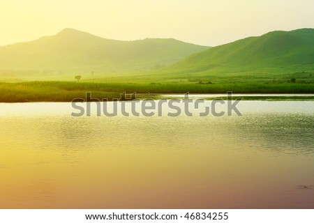 River and mountains with green grass under sunset light