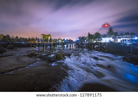 River and waterfalls at night with storm clouds and landmark