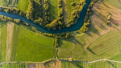River bend surrounded by fields from bird's eye view.