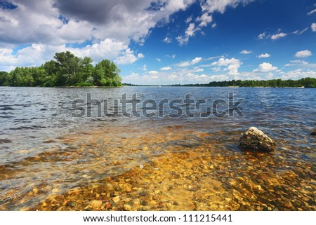 River bottom with stones in transparent water. Green island on cloudy sky background