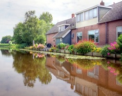 river / canal   in the Netherlands with houses on the waterside which are  giving a beautiful reflection on the water surface