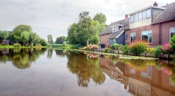river / canal in the Netherlands with traditional dutch houses on the waterside which are giving a beautiful reflection on the watersurface