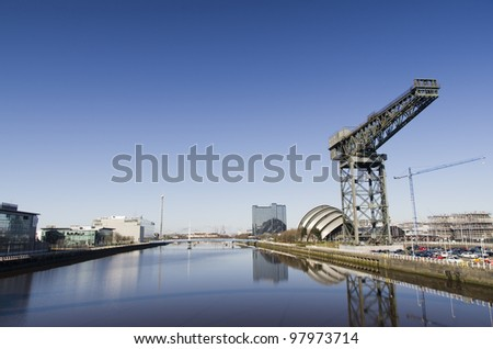 River Clyde in Glasgow with bridge, crane, auditorium and modern buildings - stock photo