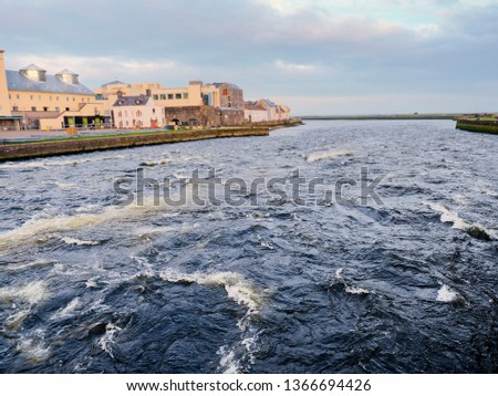 River Corrib and left bank of the river, Galwy city, Ireland. Water is high and powerful.