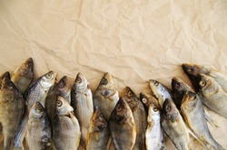 River dry salty fish on yellow crumpled paper / Dry salty fish