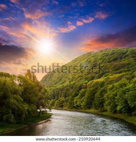 river flowing between green mountains through the forest at sunset