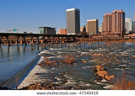 River flowing over rocks in front of a city.  Richmond, Virginia and the James River showing the bridges leading into the city.