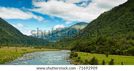 river flowing through a valley with mountain massive in the back ground