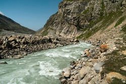 River flows through deep valley flanked by Himalayas and boulders under blue sky on bright summer day near Kaza, Himachal Pradesh, India.