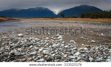 River from Fox glacier with rock foreground, New Zealand