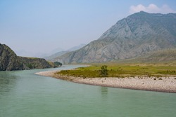 river in mountain valley, flow of water among rocks and stones with trees on shore, water tourist trip on raft