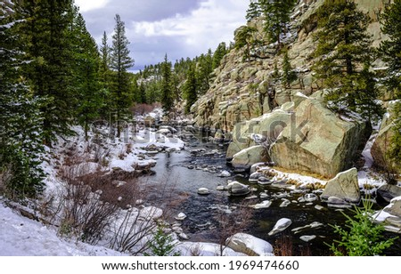River in the mountain forest. Snow on mountain forest river. River in snow mountain forest
