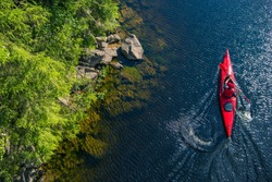River Kayaker Aerial View. Caucasian Sportsman in the Red Kayak Paddling on the Scenic River Along the Shore.