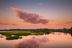 River Landscape In Belarus Or European Part Of Russia In Sunset Time Of Summer Evening. Moon Rising Over Water Lake Or River. Nature At Sunny Evening. Woods With Green Foliage On Riverside