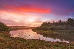 River misty autumn sunrise. Colorful dawn. Cloudy sunrise. Dusk fall colors. Riverbank with grass and bushes. Fog over lake, Belarus