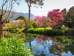 River Ninfa and medieval ruins are surrounded by amazing garden of Caetani family with flowering plants of various colors. Monti Lepini mountain valley near Norma and Sermoneta. Beautiful landscape.