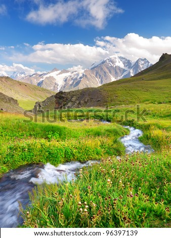 River on green meadow. High mountains and bright sky with clouds