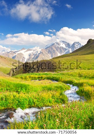 River on meadow amongst mountain valley. Natural composition