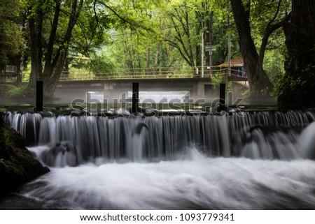 River rapids cascading over a mini dam  #1093779341