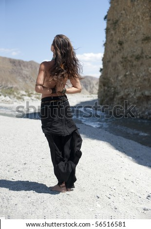 River Reverence. Beautiful young woman seen from the back standing near a desert river with her hands in a reverse yoga mudra (symbolic hand gesture).