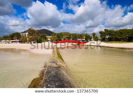 River sea hotel palm trees beach clouds sunny day, Alcudia, Majorca island, Spain