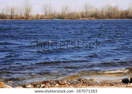 Shutterstock River stones in forest river landscape. Water surface with ripples and sunrays reflection. Summer river shore landscape