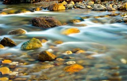 River stream water flow view. Water stnes in river stream. stream water motion