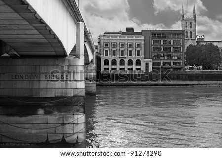River Thames running underneath the London Bridge in London, England with scenic view of old vintage stone mason building on the riverbank, in monochrome.