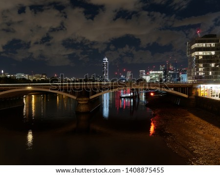 River Thames seen from the Battersea Bridge at night. A train bridge, skyscrapers, apartments, Battersea Power station Pier, and city lights are seen against cloudy sky lit by the moonlight. #1408875455