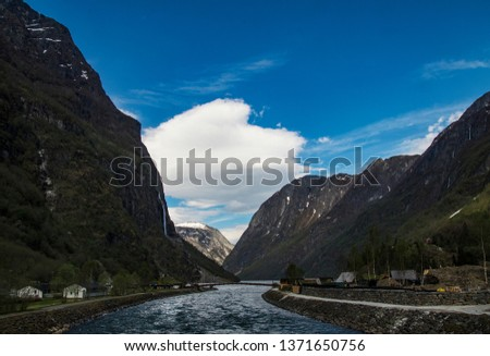 River through steep valley against blue sky. nærøydal,hill,norway,mountains,fjord,scenery,panorama,beautiful,scenic,lake,outdoor,summer,sea,view,mountain,blue,tourism,travel,water,nature,sky,landscape #1371650756