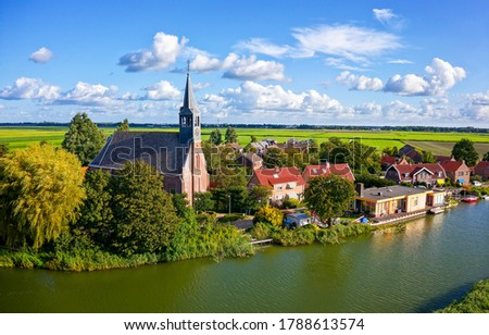 River town in sunny day. Town at river in rural landscape. Village town river landscape