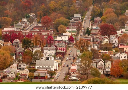 River Town USA - Aerial view of autumn in a small Kentucky river town. Two children ride bikes on the top of the grass covered floodwall between the town and the Ohio River.