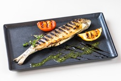 River trout grilled with tomato and lemon on a rectangular plate. Decorated with marjoram and sous
