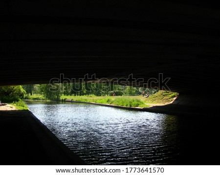 river under the bridge in the Park. Dark arch along the river. Clearance.