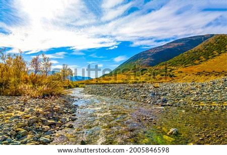 River valley among the mountain hills. Mountain river valley landscape. Mountain river valley panorama